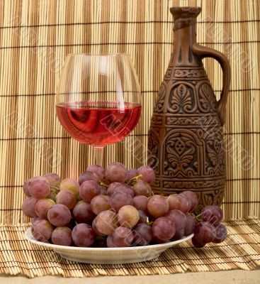 Carafe, grape and goblet on mat