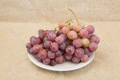 Grape on plate on textile background
