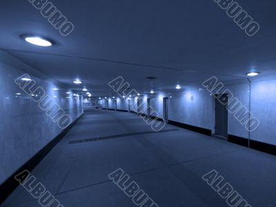 Dark concrete corridor with a closed doors