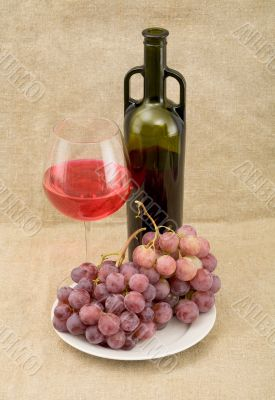 Still-life with a glass of red wine, bottle and grapes