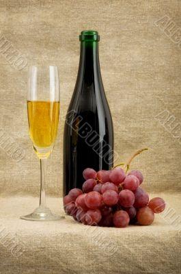 Champagne bottle, goblet, grapes