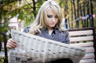 Young woman reading a newspaper