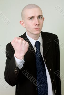 Man in a suit threatens with a fist