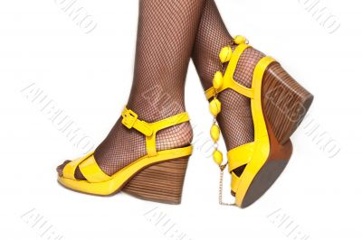 Feminine legs, yellow sandals, accessor
