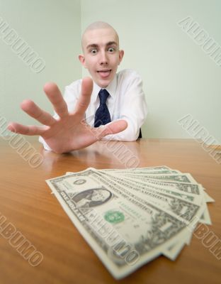 Man reaches for a batch of money