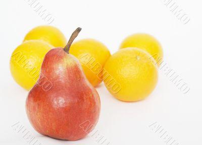 Oranges behind a red pear