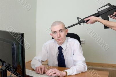 Man at office with a rifle near a head