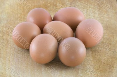 Many fresh rural eggs on the wooden surface