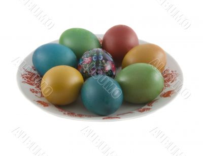 The easter decorated eggs lying in white porcelain plate with a