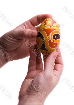 Colorful Easter egg in  hands, isolated.