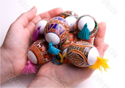 Colorful Easter eggs in palms, isolated.