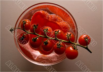 Bright red tomatoes in a bowl with water.