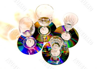 Four glasses on small colorful shiny trays.