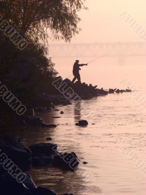 Silhouette of alone fisher near sunset river