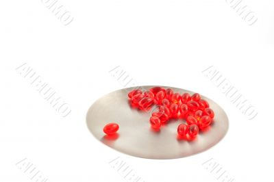 vitamin pills on a steel round plate