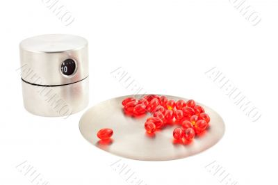 vitamin pills on a round plate and timer