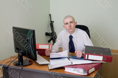 Chief on a workplace with a rifle on a background