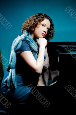 girl with fur scarf near piano thinking