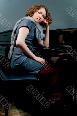 pretty young girl near piano thinking