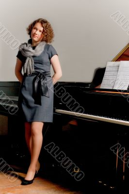 young lady in dress standing near piano