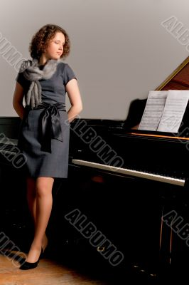 pretty young lady standing thinking near piano