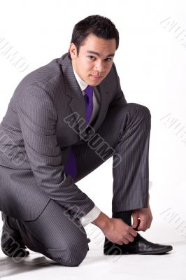 Strong young indonesian man in a suit tying his shoes