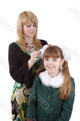 Mother is helping daughter prepare to school.