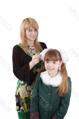 Mom is brushing young schoolgirl`s hair.