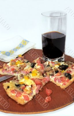 Cutting pizza and dark drink glass