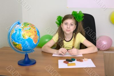 Girl sitting at a table with plasticine