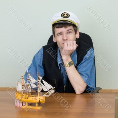 Man in a uniform cap at table with ship