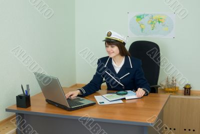 Portrait of the girl in a sea uniform at a table