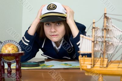 Scared girl in sea uniform at a table