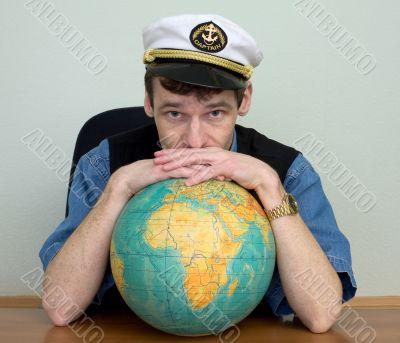 Man in uniform cap with globe
