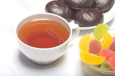 Cup with tea, a zephyr and fruit candy.