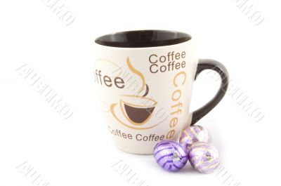 cup with text coffee with some chocolate eastern eggs next to it