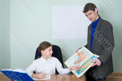 Tutor and schoolgirl with atlas