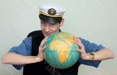 Man in a sea cap compresses globe in hands