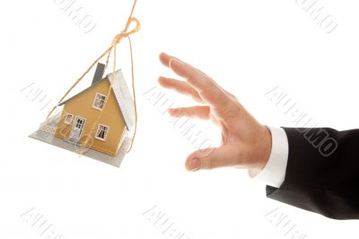 Swinging House and Business Man`s Hand Reaching or Pushing