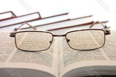 Eyeglasses on college books wisdom