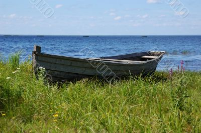 Old wooden fishing boat on the lake bank