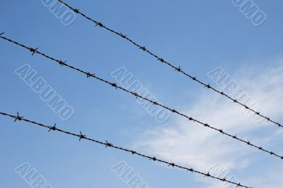 Three strands of rusty barbed wire over sky