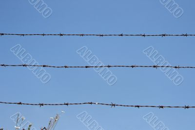Three rusty strands of barbed wire