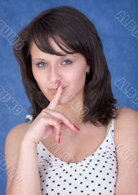 Mysterious girl with a finger near lips