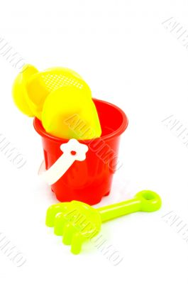 Red bucket and toys, isolated on white background