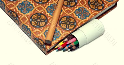 Normal pencil, tiny pencils and notebook