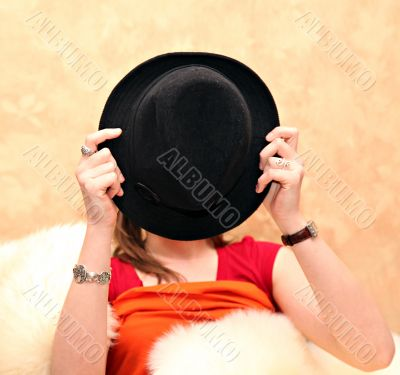 Young girl covering her face with a hat