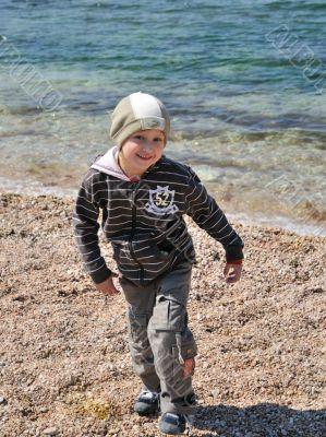little blondy boy has a fun on the beach