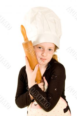 young cook wearing a chefs hat is holding a woorden rolling pin