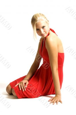 young blonde teenage girl sitting in a red dress on white